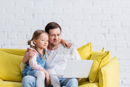 man hugging daughter while watching film on laptop at home