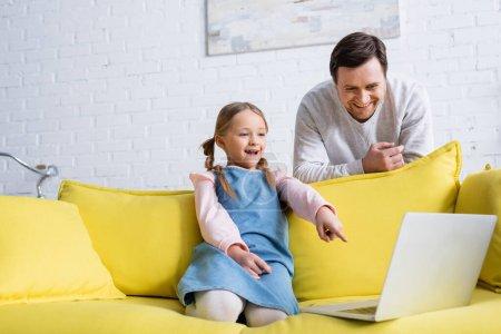 Photo pour Excité enfant pointant vers ordinateur portable tout en regardant le film près de père souriant - image libre de droit