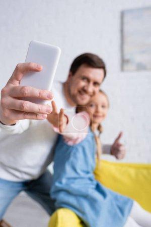 Lächelnder Mann macht Selfie mit Tochter und zeigt sich wie auf verschwommenem Hintergrund