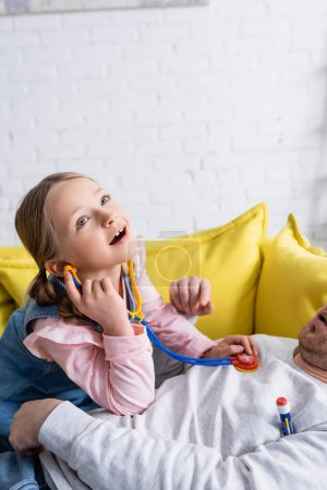girl playing doctor and examining father with toy stethoscope