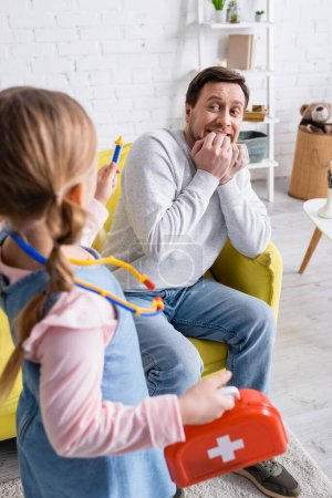 Photo for Man pretending frightened near daughter holding toy syringe on blurred foreground - Royalty Free Image
