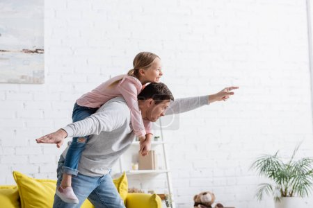 father showing fly gesture while piggybacking excited daughter at home