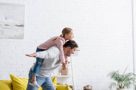 excited father piggybacking cheerful daughter at home