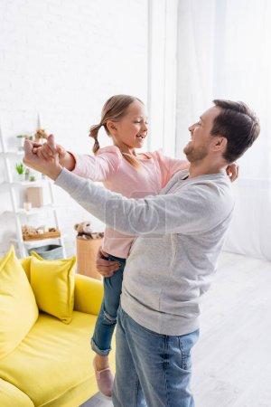 glücklicher Mann hält Tochter und tanzt zu Hause