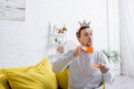 Photo pour Homme joyeux portant la couronne jouet tout en jouant prince à la maison - image libre de droit