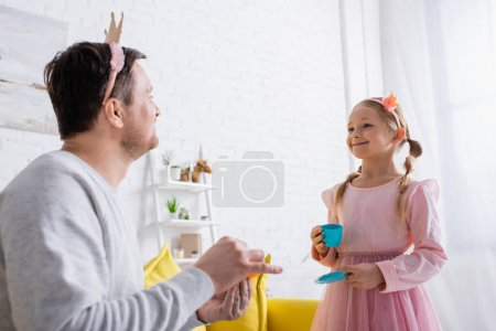 cheerful girl in toy crown looking at father on blurred foreground