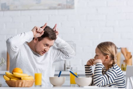 father showing bull horns gesture near daughter during breakfast