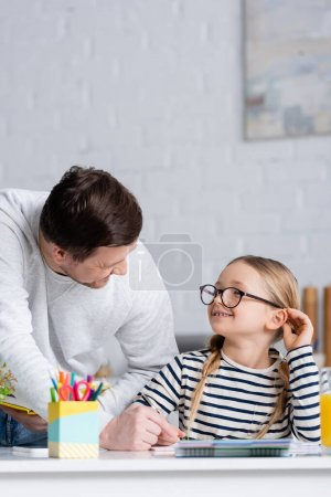 smiling girl in eyeglasses looking at father while doing homework, blurred foreground