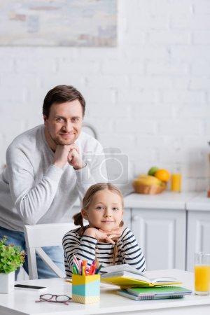 Photo pour Heureux père et fille regardant la caméra près du manuel et des cahiers sur la table - image libre de droit