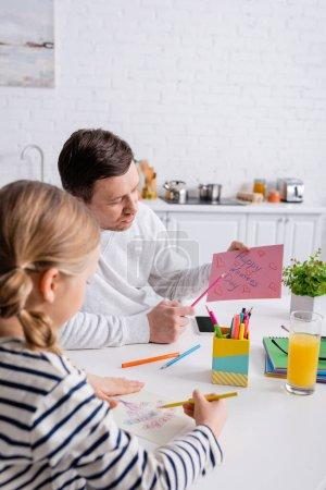 hombre señalando con la pluma en la tarjeta feliz día de las mujeres cerca de la hija dibujando en primer plano borrosa