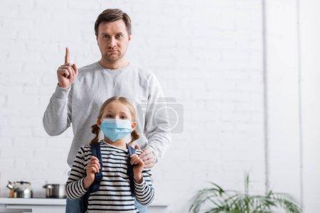 Mann zeigt Warngeste, während er in Arztmaske in die Kamera seiner Tochter blickt