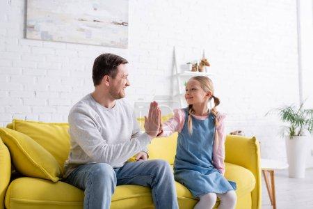 Photo pour Heureux enfant donnant haute cinq à père sur canapé à la maison - image libre de droit