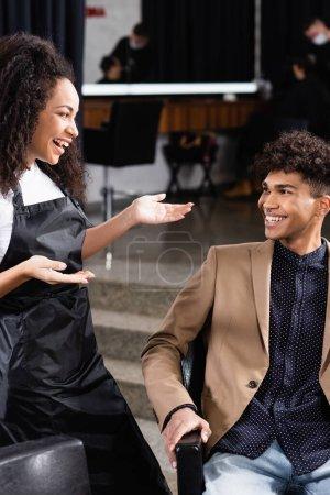 Photo pour Coiffeur afro-américain parlant à un client souriant dans le salon - image libre de droit