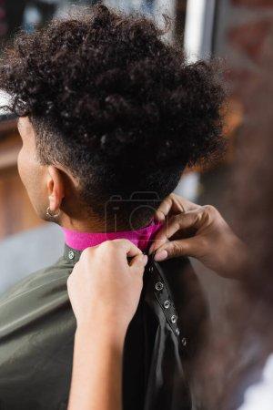 Photo pour Coiffeur au premier plan flou portant une cape sur un client afro-américain en papier collier - image libre de droit