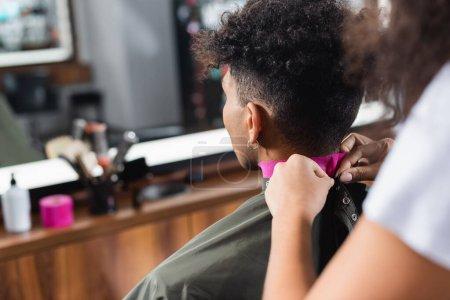 Photo pour Coiffeur portant une cape sur un client afro-américain en papier collier - image libre de droit
