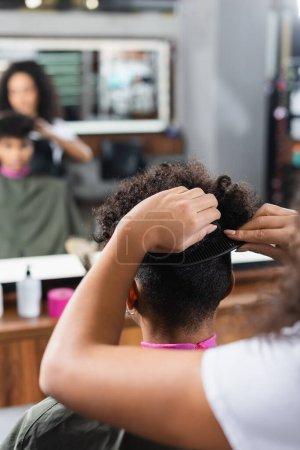 Photo pour Coiffeur afro-américain peigner les cheveux du client dans le salon - image libre de droit