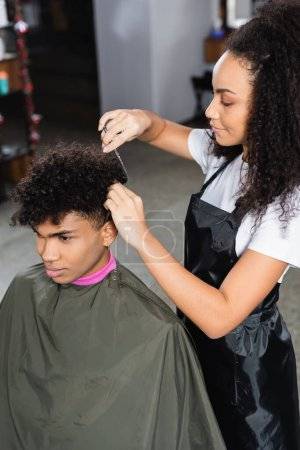 African american hairdresser cutting hair of client in cape in salon