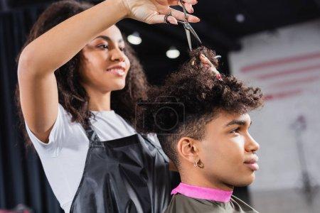 Photo pour Ciseaux en main de coiffeur afro-américain au premier plan flou travaillant avec le client - image libre de droit
