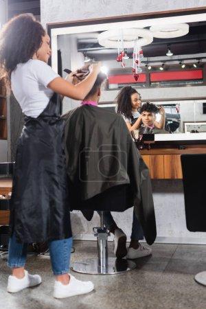 Photo pour Coiffeur afro-américain coupant les cheveux du client au premier plan flou dans le salon - image libre de droit