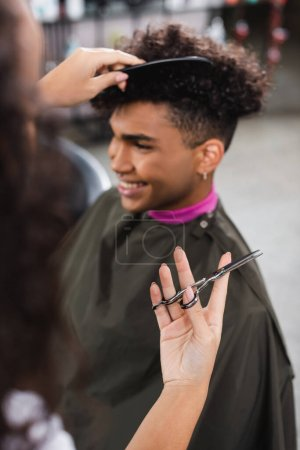 Scissors in hand of african american hairdresser combing client on blurred background