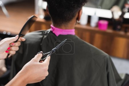 Scissors and comb in hands of hairdresser near african american man on blurred background