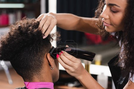 African american hairdresser trimming hair of young man