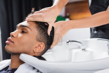 Hairstylist washing head of african american client near sink in salon