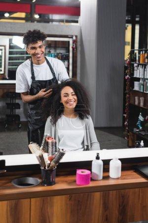 Photo pour Souriante femme afro-américaine assise près du coiffeur dans le salon - image libre de droit