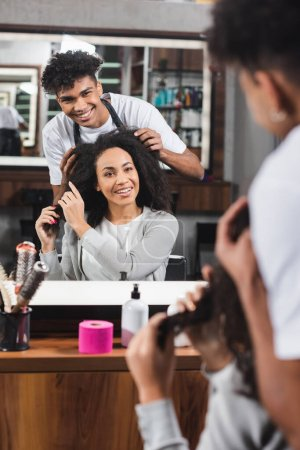 Photo for Smiling african american hairdresser and client looking at mirror in salon - Royalty Free Image