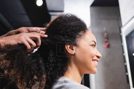 Smiling african american woman sitting near hairdresser touching curly hair