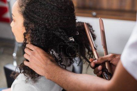 Photo pour Coiffeur afro-américain tenant lisseur de cheveux près du client - image libre de droit