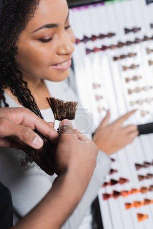 Friseur mit afrikanisch-amerikanischen Haaren und Farbmustern im Salon
