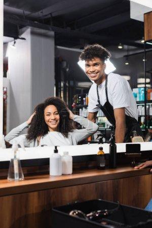 Photo pour Coiffeur afro-américain souriant et client regardant miroir dans le salon - image libre de droit
