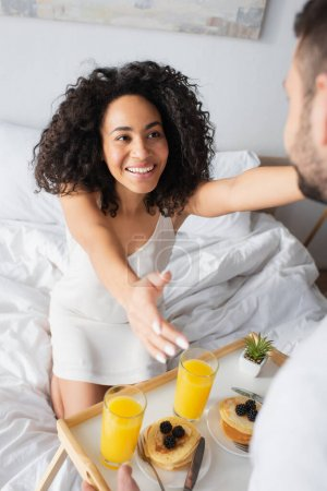 Photo for Happy african american girlfriend with outstretched hands near blurred man holding tray with breakfast - Royalty Free Image