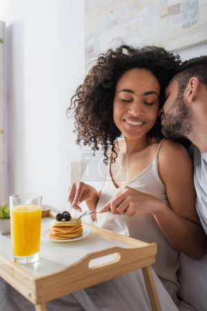 bearded man kissing happy african american woman holding cutlery near pancakes in bedroom