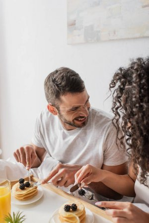 Photo for Happy bearded man holding cutlery near pancakes and looking at curly african american girlfriend - Royalty Free Image