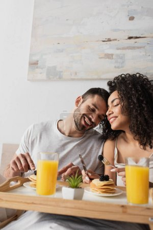 Photo for Cheerful interracial couple smiling near breakfast on tray in bedroom - Royalty Free Image