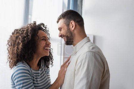 Photo for Happy interracial couple smiling while hugging at home - Royalty Free Image