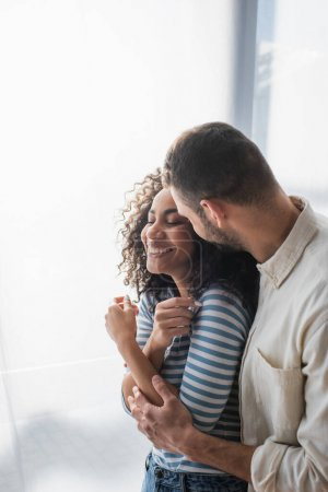 cheerful multiethnic couple smiling while hugging at home