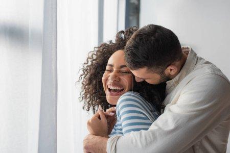 wesoła wieloetniczna para przytulająca się w domu