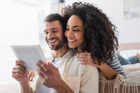 positive multiethnic couple looking at digital tablet