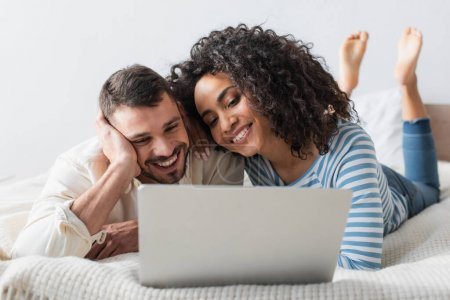 joyful interracial couple chilling on bed while watching movie on laptop