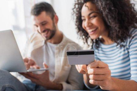 carte de crédit à la main sur femme afro-américaine gaie près de petit ami avec ordinateur portable sur fond flou