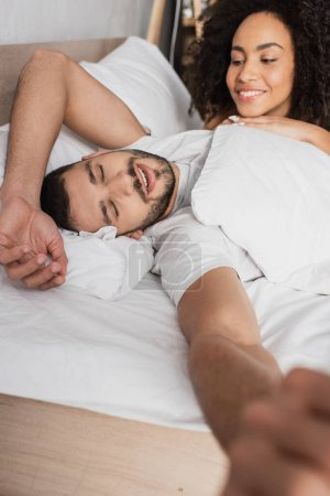 szczęśliwy Afryki amerykanka kobieta patrząc na senny chłopak w łóżku