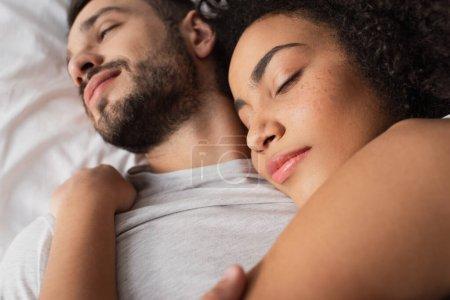 Nahaufnahme einer lockigen Afroamerikanerin, die einen bärtigen Mann umarmt und im Schlafzimmer liegt