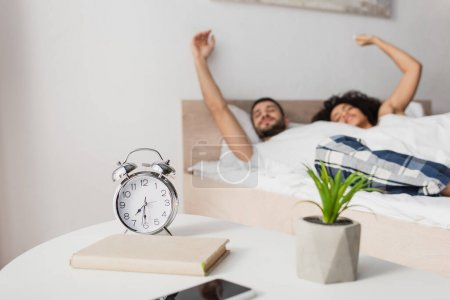 alarm clock, book, plant and smartphone on coffee table near interracial couple on blurred background
