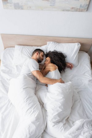 top view of interracial couple hugging and sleeping in bed