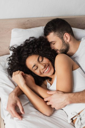 Photo for High angle view of happy multiethnic man and woman embracing while sleeping in bed - Royalty Free Image