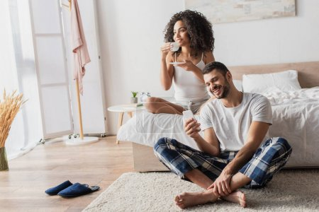 Photo for Happy african american woman holding cup with coffee while bearded boyfriend using smartphone and sitting on carpet - Royalty Free Image