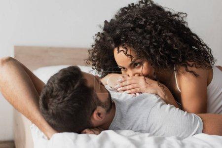 Photo pour Couple interracial couché ensemble sur le lit à la maison - image libre de droit